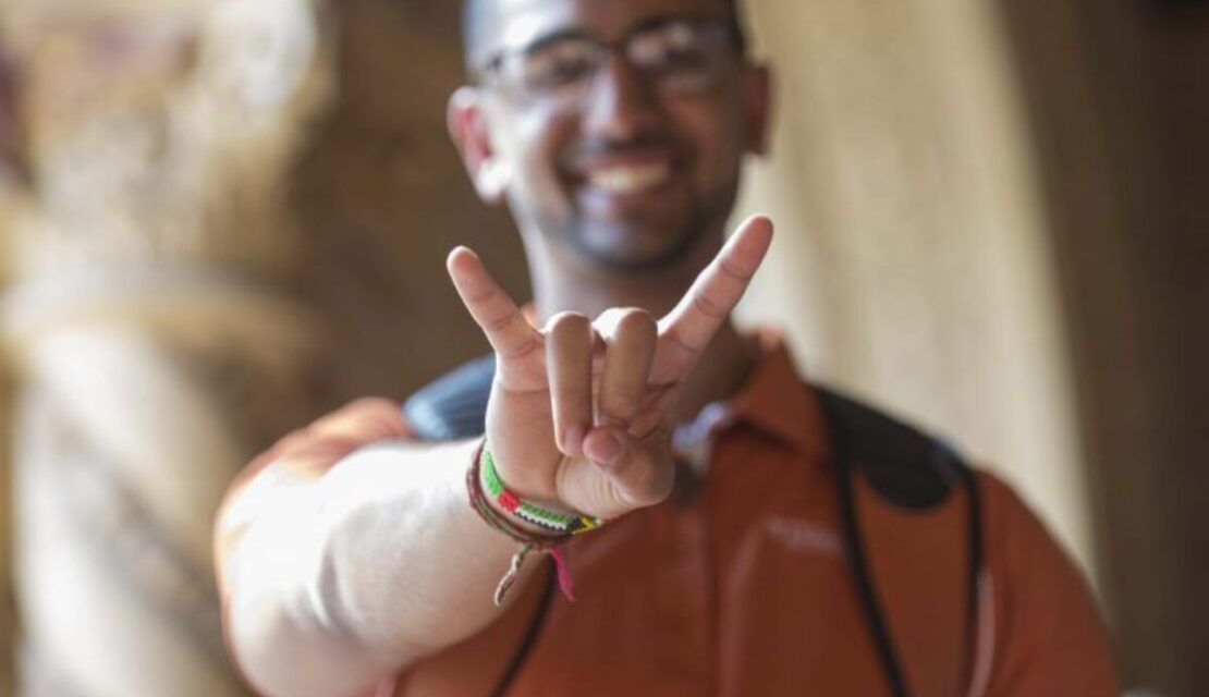 Student giving the hook 'em horns hand gesture